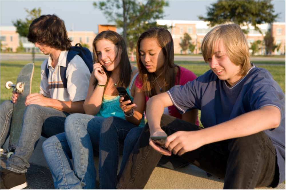 Four teens relaxing with cell phones